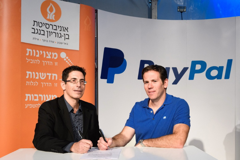 Netta Cohen, chief executive officer of BGN Technologies Ltd. (left), and Matan Parnes, PayPal's general manager in Israel, sign the agreement at the Nextech Conference at the Gav Yam Negev Advanced Technologies Park in Beer-Sheva, Israel on Wednesday, November 30th.